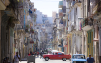 View along congested street in Havana Centro showing people walking along pavements, traffic on the road and a red American car