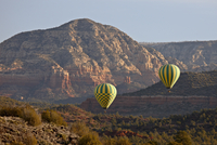 Two hot-air balloons flying low among red rock formations, Coconino National Forest, Arizona, United States of America, North Am