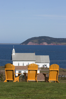 Yellow Adirondack chairs overlooking church on an island in the Gulf of St. Lawrence, Iles de la Madeleine (Magdalen Islands), Q 20025363514| 写真素材・ストックフォト・画像・イラスト素材|アマナイメージズ