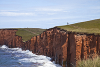 Person walking on red sandstone cliff on Cap-aux-Meules Island in the Iles de la Madeleine (Magdalen Islands), Quebec, Canada, N 20025363534| 写真素材・ストックフォト・画像・イラスト素材|アマナイメージズ