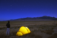 Hiker and tent illuminated under the night sky, Great Sand Dunes National Park, Colorado, United States of America, North Americ