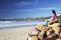 Woman sitting on rocks at St. Francis Bay, Western Cape, South Africa, Africa