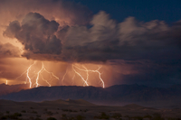 Electrical storm with forked lightning over the Grapevine mountains of the Amargosa Range, Mesquite Flats Sand dunes in the vall