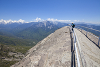 Tourist hiker, on top of Moro Rock overlooking the Sequoia foothills, looking towards Kings Canyon and the high mountains of the