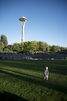 Toddler walks on lawn towards Space Needle at Seattle Center, Seattle, Washington State, United States of America, North America