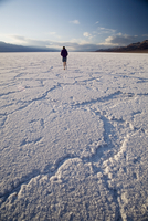 Woman walking on salt flats, Badwater Basin, at minus 282 feet the lowest point in the United States, Death Valley National Park