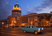 Traditional old American car speeding past the Capitolio building at night, Havana, Cuba, West Indies, Central America