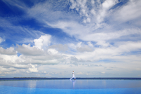 Young man meditating by infinity pool, Maldives, Indian Ocean, Asia