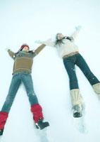 雪原に横になる2人の女性