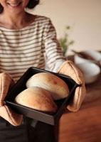 焼きたてのパンを持つ女性
