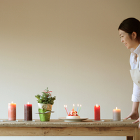 キャンドルを並べたテーブルを運ぶ女性 20027000451| 写真素材・ストックフォト・画像・イラスト素材|アマナイメージズ
