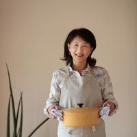 観葉植物の隣で鍋を持つ女性