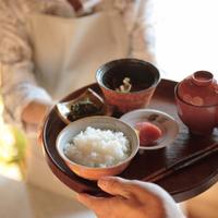 和食を渡す中高年の女性