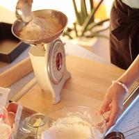 パンの材料を量る中高年の女性