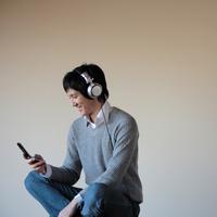 音楽を聴きながら携帯を見る20代男性