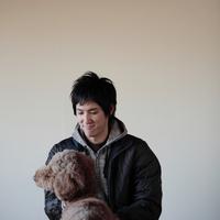 犬と戯れて微笑む20代男性