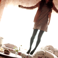 ベッドでジャンプする20代女性