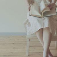 脚立に座り本を読む女性