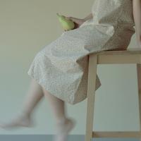 脚立に座り洋梨を持つ女性