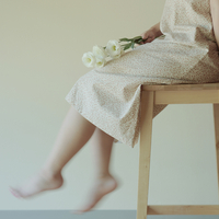 脚立に座り花を持つ女性