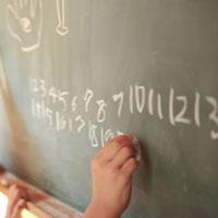 黒板に数字を書く女の子