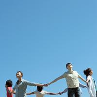 青空の下輪になって手をつなぐ若者たち