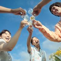 青空の下で乾杯をする若者たち