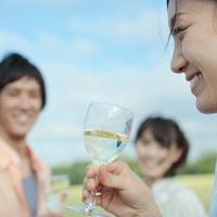 青空の下で白ワインを飲む若者たち