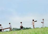 青空の下を並んで歩く若者たち