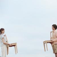 椅子を持ち向き合う2人の若者