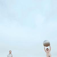 ボールを持ち上げる2人