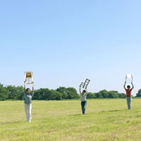 草原で椅子を持って歩く若者たち