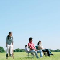 草原で椅子に座る若者たち