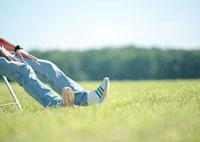 草原で椅子に座る男性の足