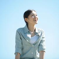 青空の下で微笑む女性