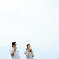 草原でコーヒーを飲むカップル