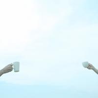 草原でコーヒーで乾杯するカップル