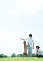 草原で犬と遊ぶカップル 20027001292A| 写真素材・ストックフォト・画像・イラスト素材|アマナイメージズ