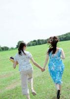 草原で手をつなぐ2人の女性