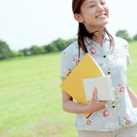 草原で本を持つ女性
