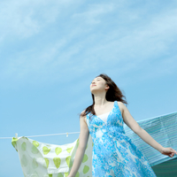 青空の下風を感じる女性