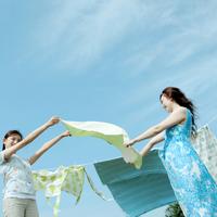 草原で洗濯物を干す2人の女性