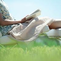 草原で本を読む中高年の女性