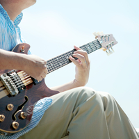 草原でギターを弾く中高年の男性