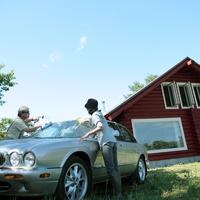 車を洗うシニア夫婦とログハウス