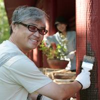 ログハウスのペンキを塗る中高年男性