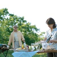外で食事の準備をするシニア夫婦