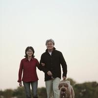 草原を散歩するシニア夫婦と犬 20027001480| 写真素材・ストックフォト・画像・イラスト素材|アマナイメージズ