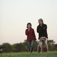 草原を散歩するシニア夫婦と犬 20027001481| 写真素材・ストックフォト・画像・イラスト素材|アマナイメージズ