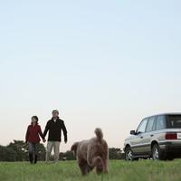 草原を散歩するシニア夫婦と犬 20027001483| 写真素材・ストックフォト・画像・イラスト素材|アマナイメージズ